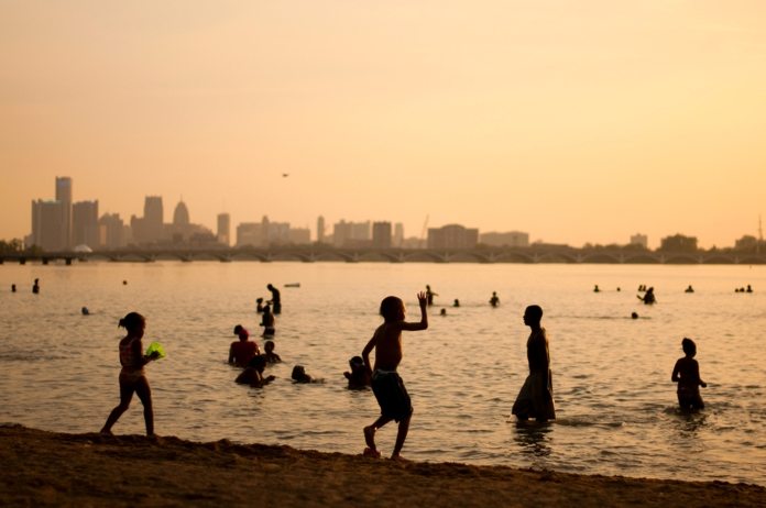Children play into the evening during a heat wave on the Belle Isle beach, an island located in the Detroit River between Canada and Detroit