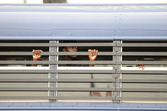 A teenager looks out of a Detroit Police bus after being detained for curfew violation on Monday evening ahead of the annual fireworks display, June 23. (Tanya Moutzalias/Special to the Detroit News)