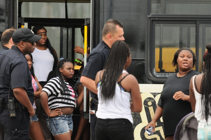 A teenage girl looks in disgust as her and her friends stand on the edge of the bus Detroit Police are using to detain and transport minors for curfew violation on Monday evening ahead of the annual fireworks display, June 23. (Tanya Moutzalias/Special to the Detroit News)