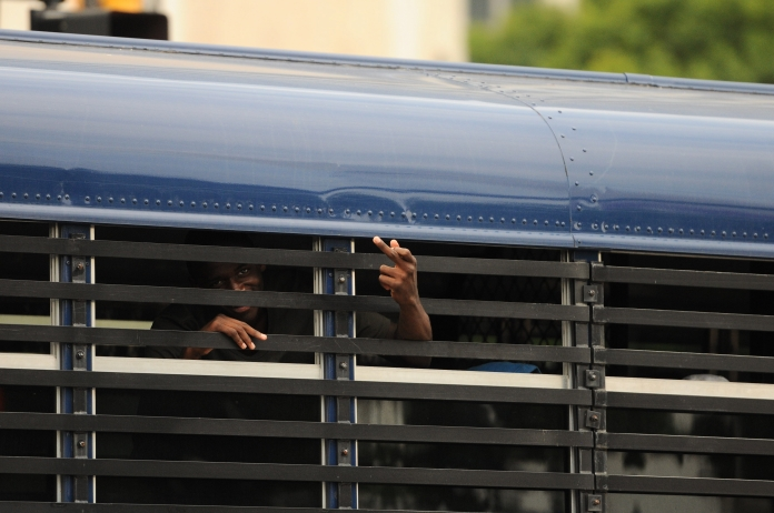 A teenager boy throws his middle finger up as a Detroit Police bus drives away. Minors were being detained for curfew violations on Monday evening ahead of the annual fireworks display, June 23. (Tanya Moutzalias/Special to the Detroit News)