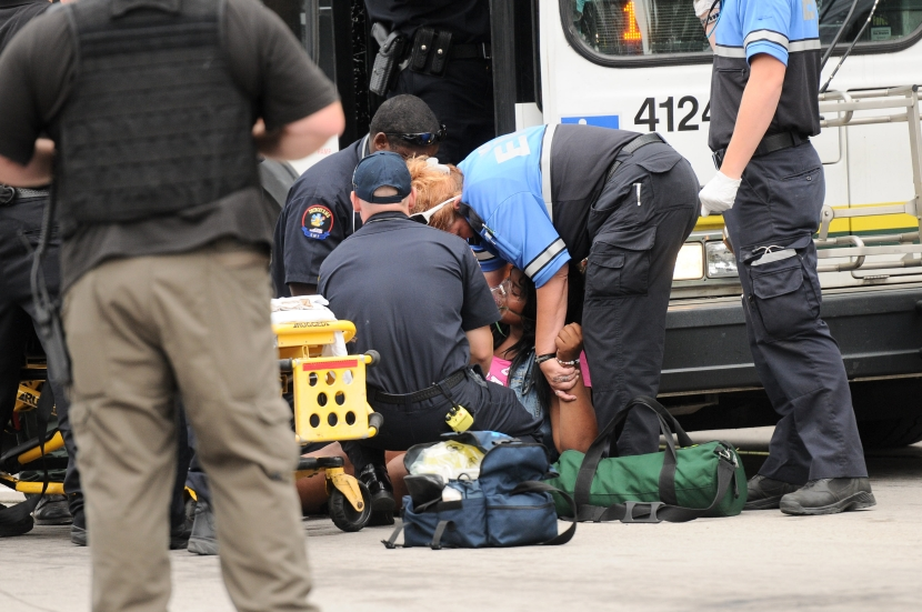 A teenage girl gets assistance from EMS crews after she repeatedly tried to catch her breath using an inhaler after Detroit Police daughter her for curfew violation on Monday evening ahead of the annual fireworks display, June 23. (Tanya Moutzalias/Special to the Detroit News)