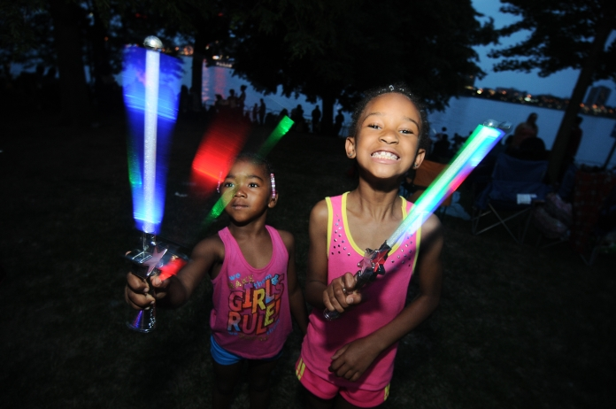 (left) Sayniya, 4, and Kynoriana, 8 of Detroit, play with glow wands ahead of Monday night's annual firework display in Hart Plaza, June 23. (Tanya Moutzalias/Special to the Detroit News)