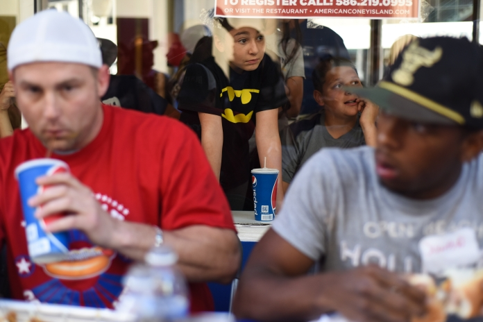 A young girl watches from inside American Coney Island as participants compete in the Coney Dog Eating contest Thursday in downtown Detroit, Aug. 28. (Tanya Moutzalias/ Special to the Detroit News)