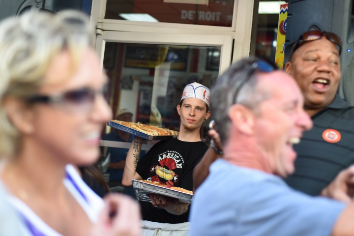 A server waits with more trays of hot dogs to be delivered as the competition grows closer between 3 hungry participants in the 4th annual American Coney Island Coney Dog Eating contest Thursday in downtown Detroit, Aug. 28. (Tanya Moutzalias/ Special to the Detroit News)