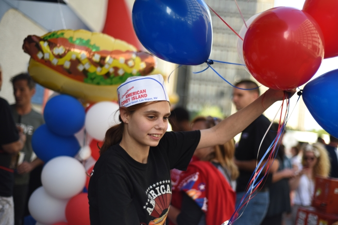 Chelsea Blessing, 19 of River Rouge, carries extra balloons outside during the 4th annual American Coney Island Coney Dog Eating contest Thursday in downtown Detroit, Aug. 28. (Tanya Moutzalias/ Special to the Detroit News)