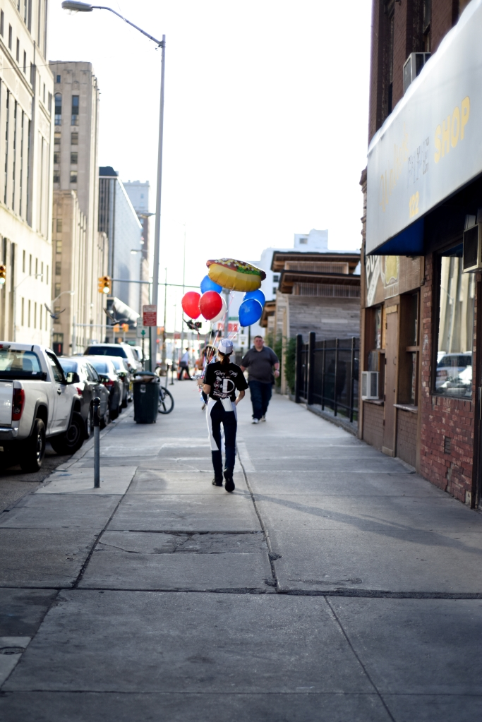 Ameircan Coney Island employee Chelsea Blessing, 19 of River Rouge, carries extra balloons down the street during the 4th annual American Coney Island Coney Dog Eating contest Thursday in downtown Detroit, Aug. 28. (Tanya Moutzalias/ Special to the Detroit News)