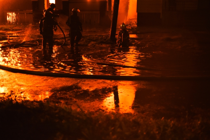 Detroit Firefighters stand in nearly knee-deep water as they fought an abandon dwelling fire at 3140 E. Kirby St. between Elmwood and McDougall St. on Detroit's near east side just after midnight on Devil's Night Oct. 31, 2014.