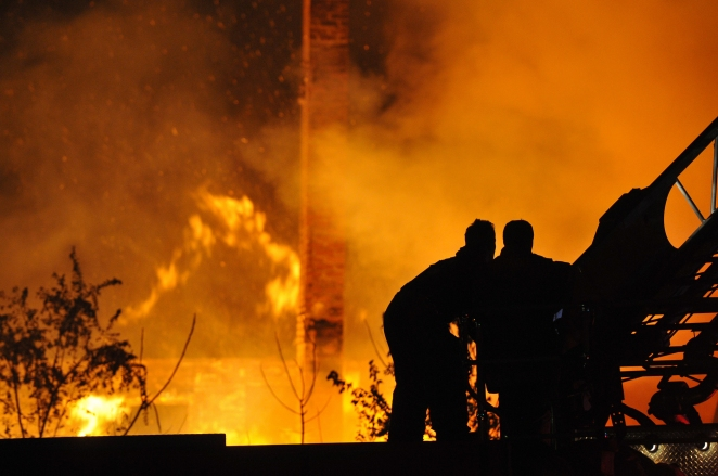 Two Detroit Firefighters control a tower ladder from atop their engine at two abandon dwelling fires at Mt. Elliot and E Warren just after midnight on Devil's Night Oct. 31, 2014. At the same time and less than a mile away DFD fought two other vacant dwelling fires. (Tanya Moutzalias/ Special to the )