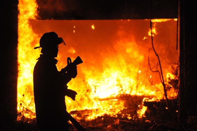 A Detroit Firefighters prepares to use the hose on a fire that spread into abandon third structure at Mt. Elliot and E Warren just after midnight on Devil's Night Oct. 31, 2014. At the same time and less than a mile away DFD fought two other vacant dwelling fires. (Tanya Moutzalias/ Special to the )