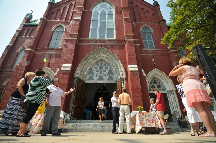 Church-goers spill outside of the packed St. Albertus Church on Sunday morning, Aug. 10. Detroit Mass Mob brought Church-goers from all over Metro Detroit, who filled the pews, aisles and spilled outside the doors at St. Albertus Church. (Tanya Moutzalias/ Special to the Detroit News)