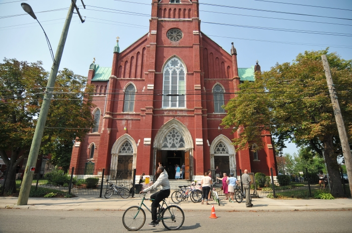 A man raises his hand as he rides past Detroit's oldest Polish Church, St. Albertus on Sunday morning. Detroit Mass Mob brought Church-goers from all over Metro Detroit, who filled the pews, aisles and spilled outside the doors at St. Albertus Church on Sunday, Aug. 10. (Tanya Moutzalias/ Special to the Detroit News)