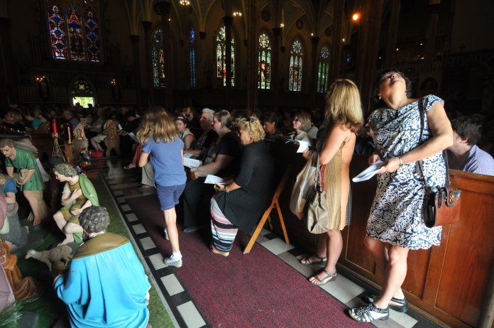 A church-goer looks up at St. Albertus Church's ornate ceiling and stained glass windows. Detroit Mass Mob brought Church-goers from all over Metro Detroit, who filled the pews, aisles and spilled outside the doors at St. Albertus Church on Sunday Aug. 10 (Tanya Moutzalias/ Special to the Detroit News)