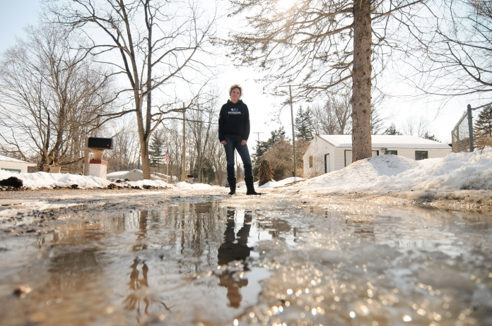 Sharon Chapman stands on her street Shannon Dr., a private road in Hamburg Township on Friday, March 14. Due to the high temperatures the snow melt has turned her street into a river of running water. Chapman lives in a flood-prone area along the Huron river. Tanya Moutzalias/Special to the Free Press