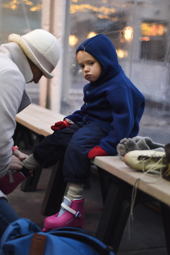 FEA - Three and a half year-old Thea Sugar sits on the bench while her mom Jane Sugar, of Detroit, helps her put on her skates during Friday evening's preseason ice skating opening at the ice rink in Campus Martius Park Downtown Detroit, Nov. 14, 2014.
