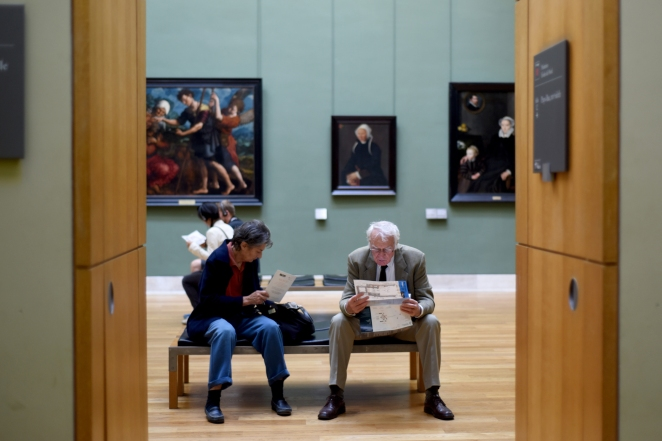 FEA - A man looks over the map of the Louvre's collection while resting in the Flemish paintings section, Sept., 2014.