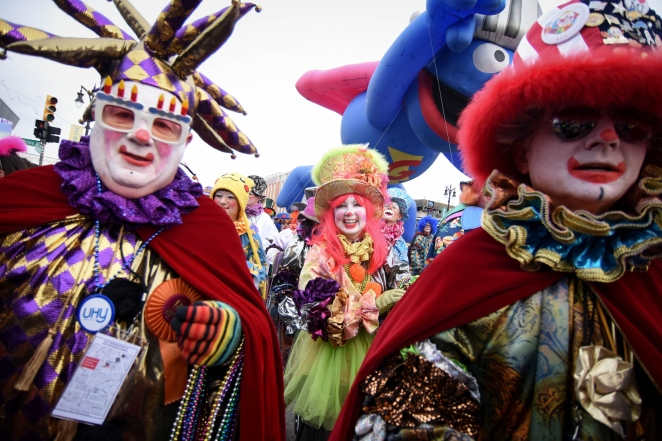 FEA - The Distinguished Clown Corps are a parade favorite, throwing out 300,000 beads to the crowd, during the 88th America's Thanksgiving Parade on Woodward Ave. in Detroit's Midtown Thursday morning Nov. 27, 2014.