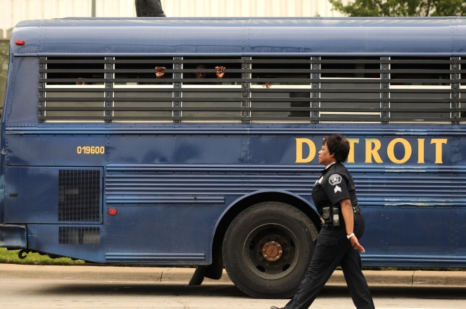 GN - Young men look out of a Detroit Police bus after being detained for curfew violation on Monday evening ahead of the annual fireworks display, June 23, 2014.