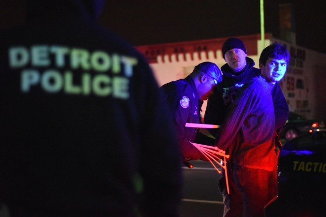 SN - A protestor is arrested while marching down Gratiot Ave. on Detroit's eastside, shutting down the street during a rally for Ferguson Tuesday night, Nov. 25, 2014. Two majors protests sparked up over the city, effectively shutting down traffic on 3 different major freeways.