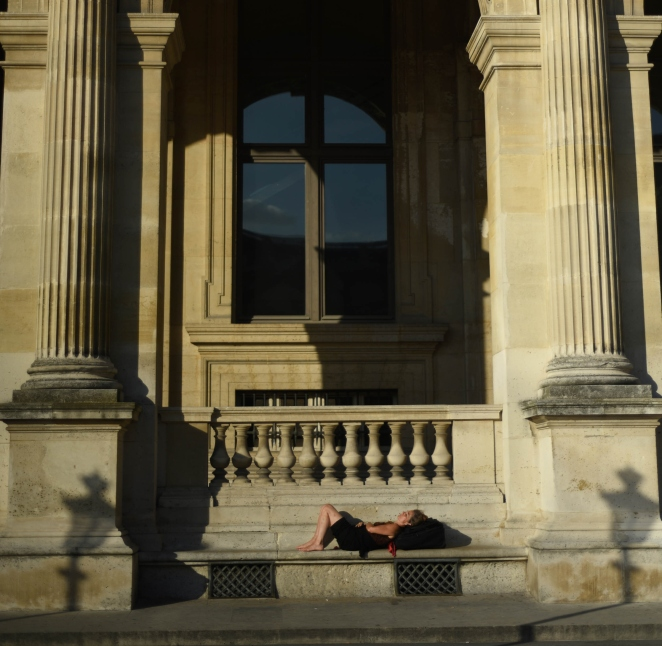 PV - A women takes a nap in the late afternoon sun outside of the Louvre Museum in Paris, France on a warm September day.