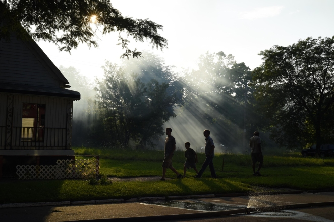 PV - Smoke filters through the afternoon sun as a fire burns a vacant home on Detroit''s Old Poletown neighborhood. A family came to see the flames which brought the smoke that could be seen from miles away, Aug. 30, 2014.