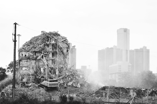 PV - The final tower of the Brewster-Douglass Housing Projects is demolished as the Renaissance Center, General Motors' world headquarters, is masked in its dust, Aug. 21, 2014. The low-income Brewsters sprawled over 14-acres of land and were most notable for being the childhood home of Diana Ross and Lily Tomlin. Crime and drugs took over the project as Detroit's population decreased; its last tenets left in 2008. The Brewsters sat vacant for years until its demolition 6 years later in 2014 as Detroit looked to find its way out of bankruptcy.