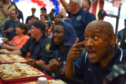 (right) Detroit Fire Department Captain Chris Dixon smears coney sauce on his face. Thursday evening American Coney Island hosted the 2015 Coney Dog Eating Challenge. The eating challenge began with a competition between the Detroit Police Detroit and the Detroit Fire Department, with the police taking home the title. (Tanya Moutzalias | MLive.com Detroit)
