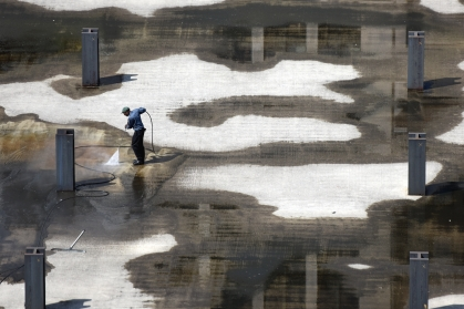 A man power washes the cement where Hudson's used to stand May 11, 2015. (Tanya Moutzalias   MLive Detroit)
