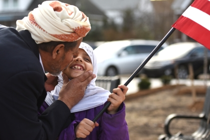 Ngi Pedy, of Hamtramck, kisses Zohowr Almasmirari, 8, on the check as she holds an American flag at a rally against terrorism in Hamtramck, Mich. Friday afternoon Dec. 11, 2015. (Tanya Moutzalias   MLive Detroit)