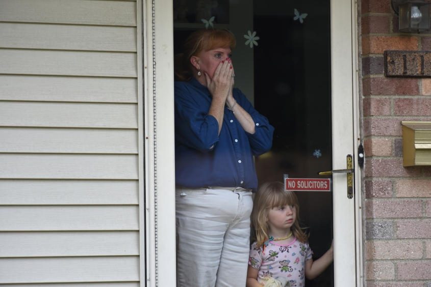 Kendall Randazzo, of Warren, and her daughter Kendall, 3 1/2, reacts to seeing their neighbor's house across the street destroyed in a fiery explosion. An explosion and fire on the 11900 Harold and Rubin Rd. in a house in Warren, Michigan erupted just after 1 p.m. on Monday, Sept. 28, 2015. The family who lived in the home were not there at the time, neighbors rescued the two dogs from the yard, one cat was killed in the fire. (Tanya Moutzalias | MLive Detroit)