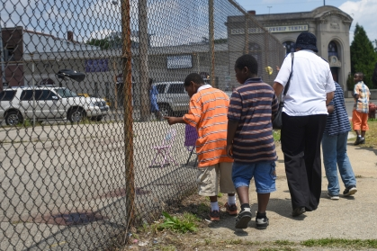 A young boy, who came with family to pray with Salvation Army Temple Corp church, points to the dried pool of blood where Saturday night 12 people were shot, one fatally, during a block party on a basketball court on Dexter and Webb St. on Detroit's west side Sunday June 21, 2015. Over 400 people were estimated to be in attendance at the block party including children. The victims ranged from 19- to 47-year-old. Forty-seven shots were fired from at least three guns during, what is being called a retaliation-style mass shooting, Saturday night. (Tanya Moutzalias | MLive Detroit)