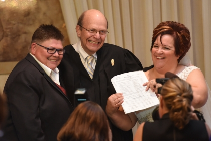 (left) Jayne Rowse and April DeBoer hold up their signed marriage certificate during a wedding ceremony in Southfield, MI Saturday, Aug. 22, 2015. (center) U.S. District Judge Bernard Friedman performed the ceremony. The judge overheard the coupleÕs case when they were changeling MichiganÕs adoption laws before being thrust into the battle for same-sex marriage rights, overturning Michigan's ban on gay marriage. (Tanya Moutzalias | MLive Detroit)