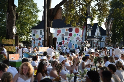 "Hundreds of guests, dressed in all white, gathered for this yearÕs elusive ÔD""ner en BlancÕ held DetroitÕs Heidelberg Project Sunday evening, Aug. 16, 2015. The eveningÕs date, time and location are held in close secrecy before the event. Invited guests and their dinner party friends are instructed to bring their own tables, chairs, food, drink and of course white table cloth. The attire- all white and Ôformal.Õ Now in its fifth year the Detroit ÔD""ner en BlancÕ is modeled from a pop-up dinner party originating in Paris in 1988 and has now spread across the world. (Tanya Moutzalias 
