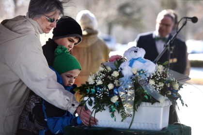 (left) Community member Andrea Goodison, of Sterling Heights with her grandchildren (left) Liam O'Brien, 8, and Sean O'Brien, 5, pay their respects at the funeral of Henry Alexander Macomb, the name unofficially given to the infant boy whose body was found in a Roseville recycling center. Goodison brought her grandchildren Roseville police and firefighters alongside with community members paid their respects at the funeral at held at Resurrection Cemetery Wednesday morning, March 11, 2015. (Tanya Moutzalias | MLive Detroit)
