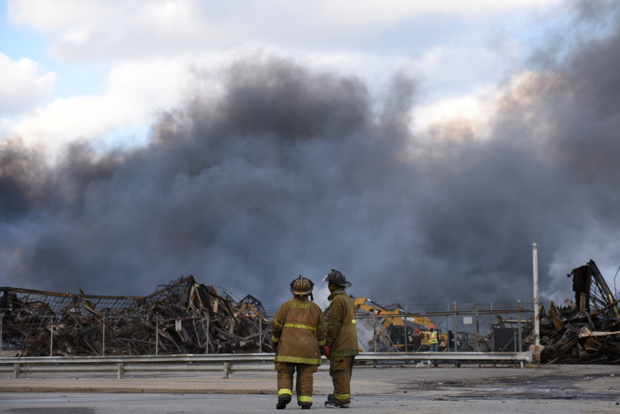 Heavy smoke continues to billow from a massive warehouse at Hamilton Ave. and Manchester Pwky in Highland Park, Mich. just after 5 p.m. Wednesday. A multiple alarm fire broke out inside the warehouse around 2:30 a.m Wednesday, Feb. 3, 2016. Officials said the fire could potentially continue burning for days. (Tanya Moutzalias | MLive Detroit)